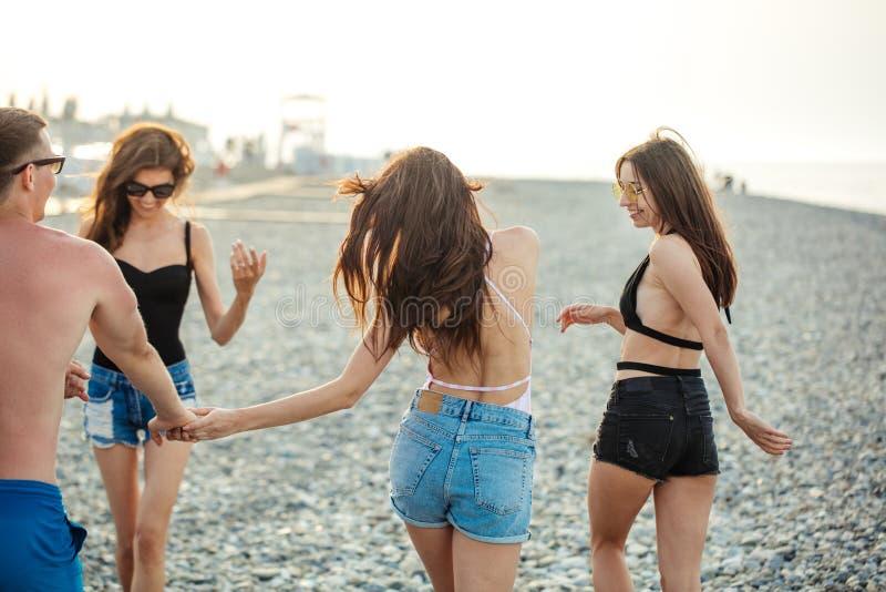 Vrouwen die langs kustlijn wandelen vrouwelijke vrienden die samen op strand lopen, die de zomer van vakantie genieten royalty-vrije stock afbeeldingen