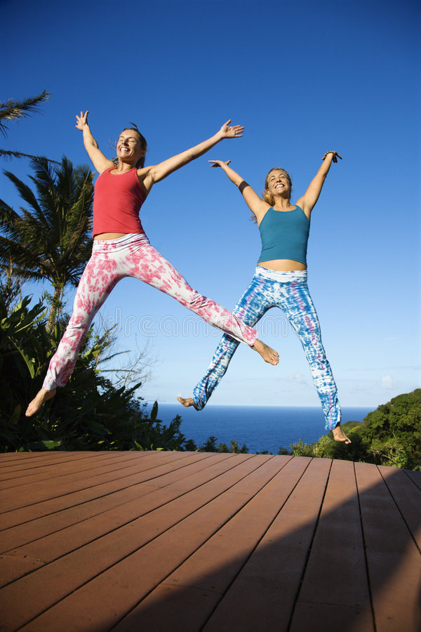 Vrouwen die in lucht springen. stock afbeeldingen