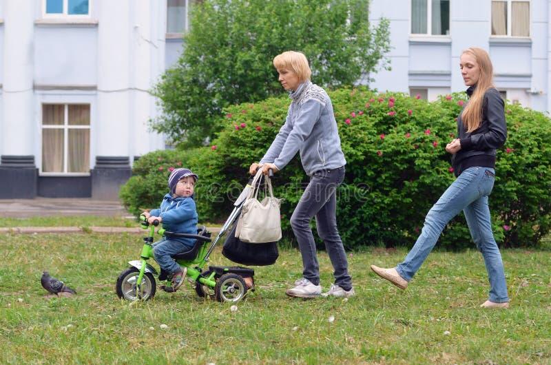 Vrouwen die met een klein kind op een Fiets op het gras in Th lopen stock afbeelding