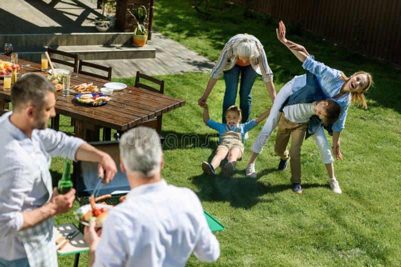 Vrouwen die met jonge geitjes spelen terwijl mannen die vlees koken tijdens barbecue royalty-vrije stock foto's