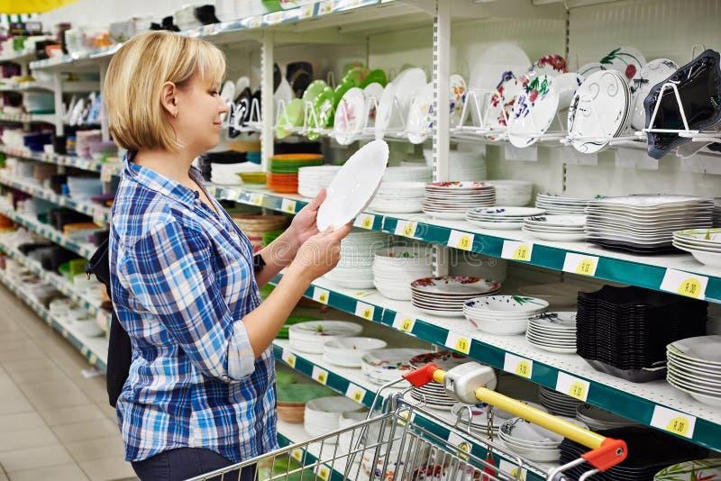 Vrouwen die met kar koopt plaat in opslag de winkelen stock afbeeldingen