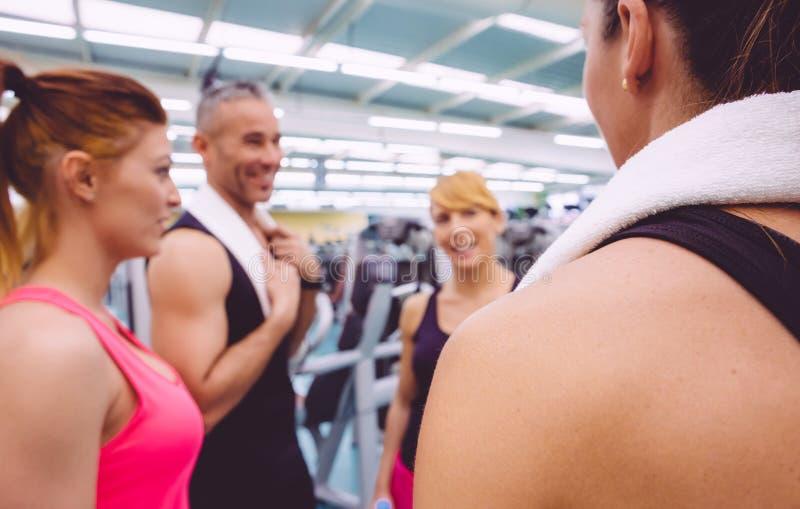 Vrouwen die met persoonlijke trainer na opleiding spreken stock foto