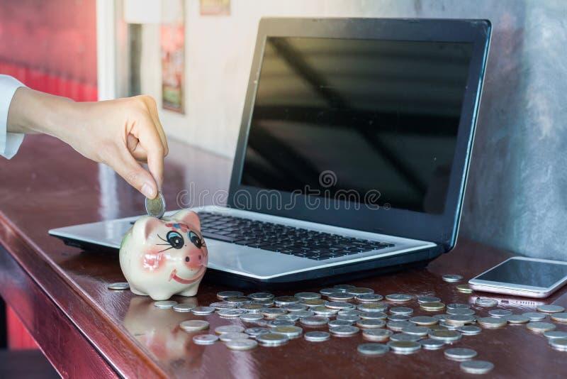 Vrouwen die muntstuk in spaarvarken zetten besparingsgeld, stock fotografie