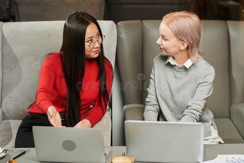 Vrouwen die online aan laptop werken stock foto