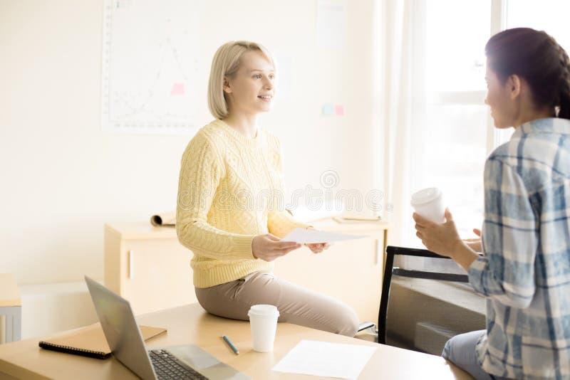 Vrouwen die op bureau zitten die in bureau spreken stock fotografie