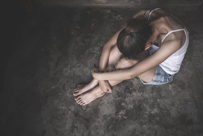 Vrouwen die op de vloer zitten die met depressie, Gedeprimeerde vrouw, familieproblemen, Spanning, keuken, misbruik, Huiselijk ge stock foto