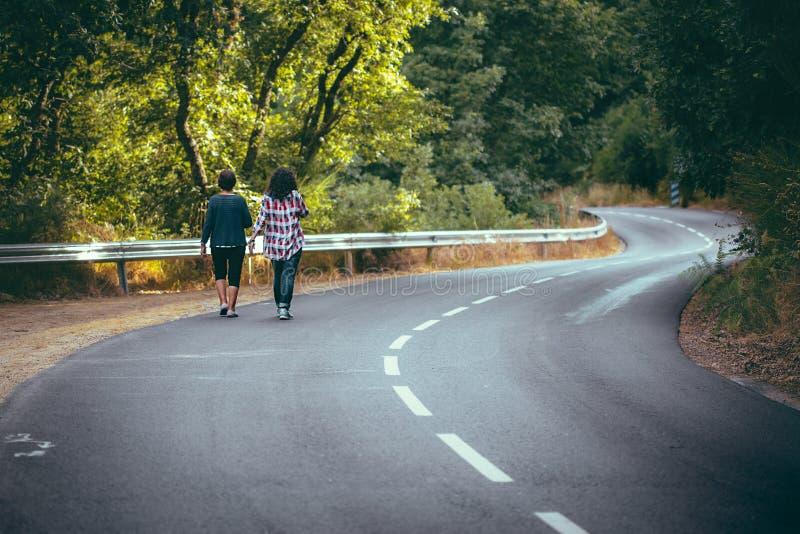 Vrouwen die op de weg lopen die mooi bos kruisen stock afbeeldingen