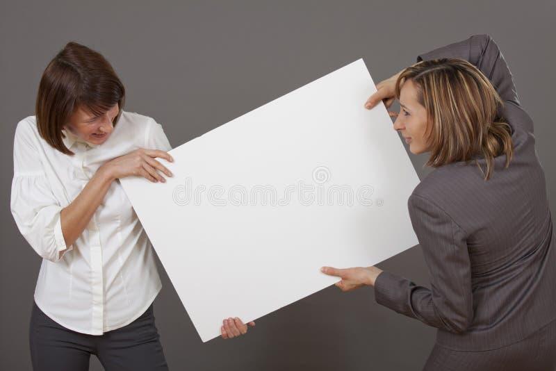 Vrouwen die over witte raad vechten stock foto's