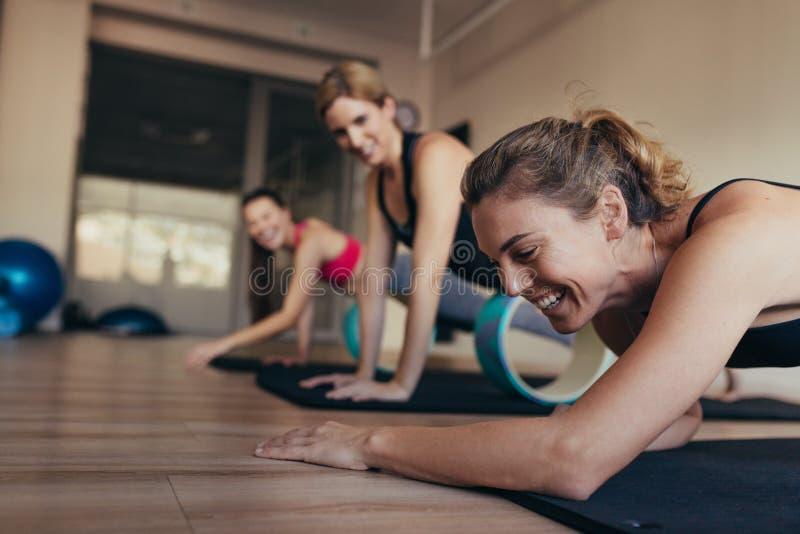 Vrouwen die pret hebben terwijl het doen van pilates training royalty-vrije stock foto