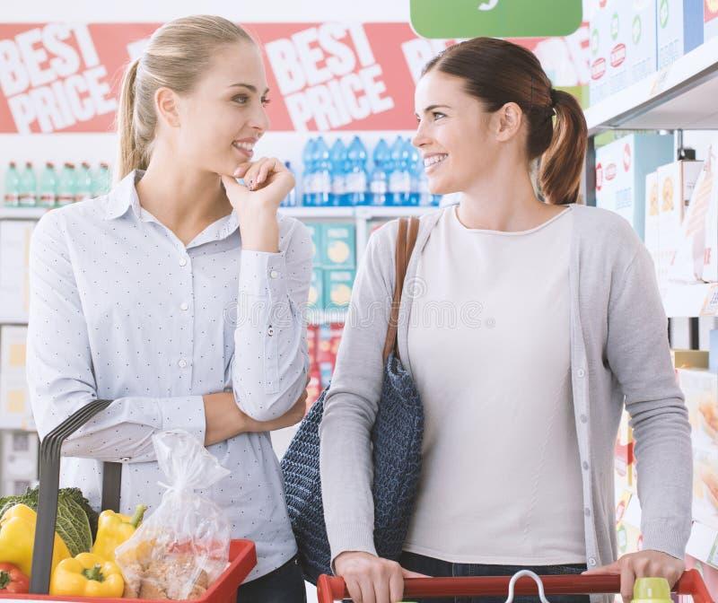 Vrouwen die samen bij de supermarkt winkelen stock afbeeldingen