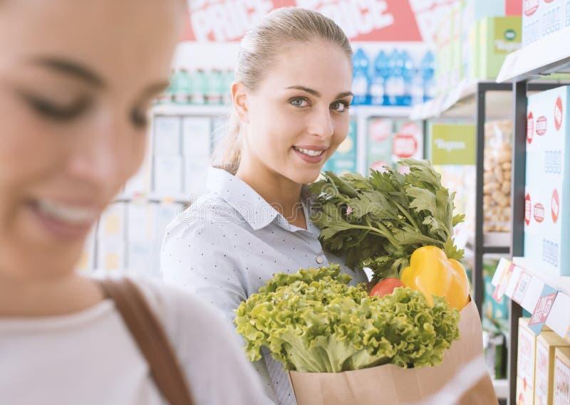 Vrouwen die samen bij de supermarkt winkelen royalty-vrije stock afbeeldingen