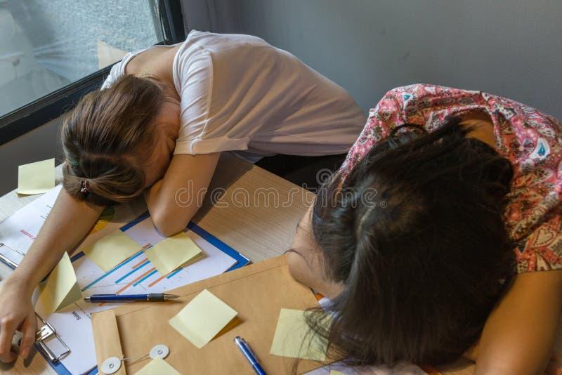 Vrouwen die in slaap op bureauhoogtepunt van documenten, kleverige nota's vallen stock foto's