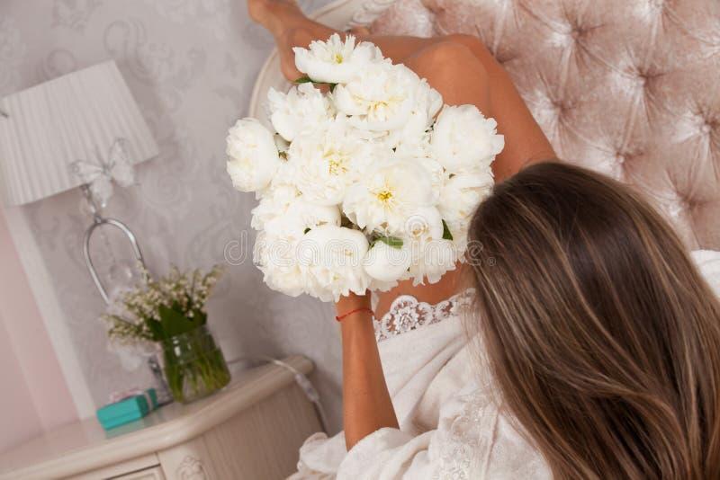 Vrouwen die in slecht met boeket van witte pioenen ontspannen royalty-vrije stock afbeelding