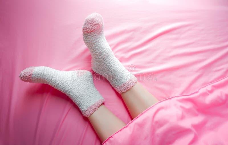 Vrouwen die sokken op de winterochtend en dekensachtergrond dragen Warm en comfortabel op beddegoedblad stock afbeeldingen