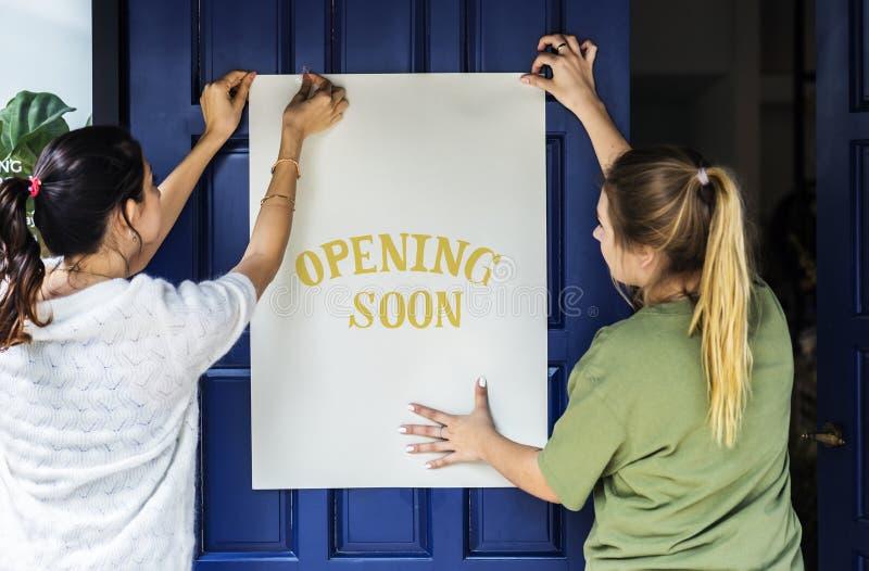 Vrouwen die spoedig openend teken op een voordeur zetten stock fotografie