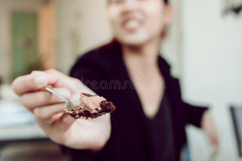 Vrouwen die stuk van chocoladecake eten met een vork terwijl het zitten bij een koffielijst stock foto