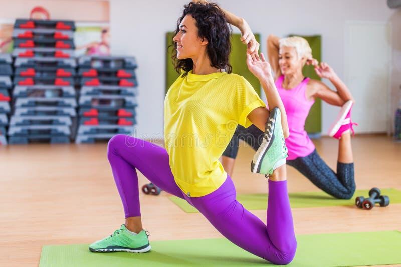 Vrouwen die uitrekkende yogaoefeningen op mat binnen in gymnastiek doen stock afbeelding