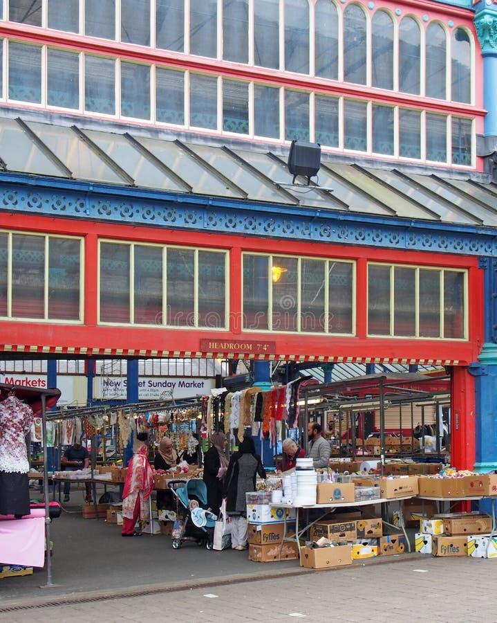 vrouwen die voor stof en naaiende materialen op een box in huddersfieldmarkt winkelen in West-Yorkshire royalty-vrije stock afbeelding