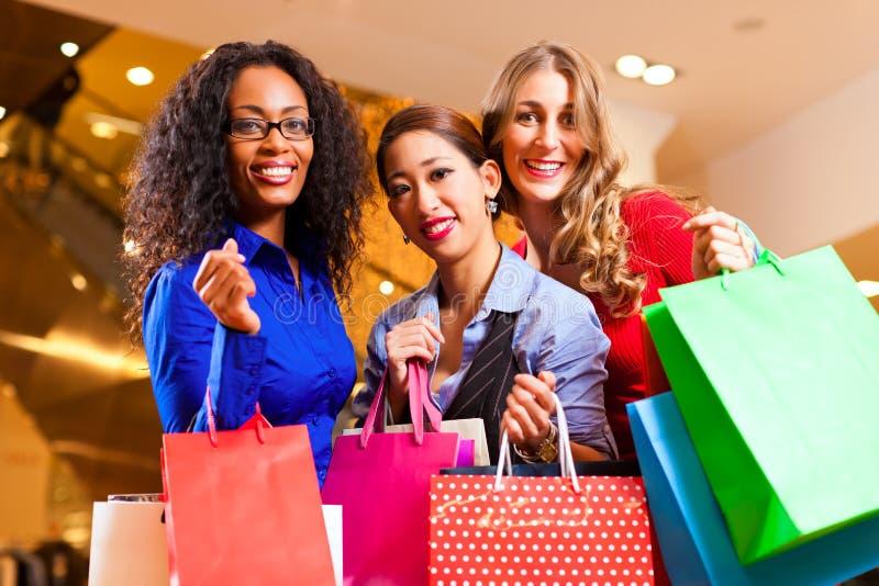 Vrouwen die in wandelgalerij met de decoratie van Kerstmis winkelen stock afbeelding