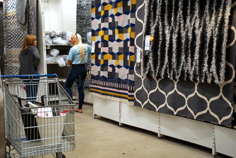 Vrouwen die winkelen voor tapijten stock fotografie