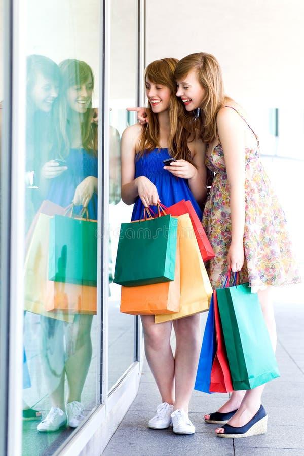 Vrouwen die in winkelvenster kijken royalty-vrije stock afbeeldingen