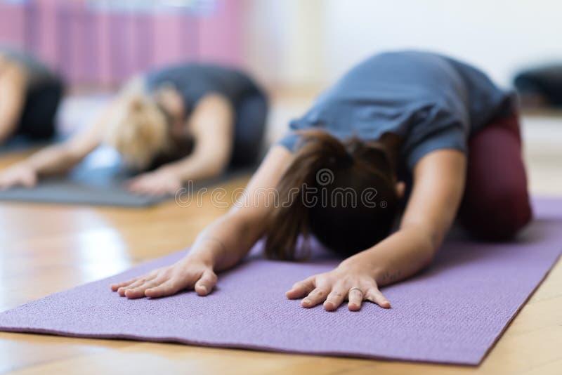 Vrouwen die yoga doen die samen opleiden stock foto