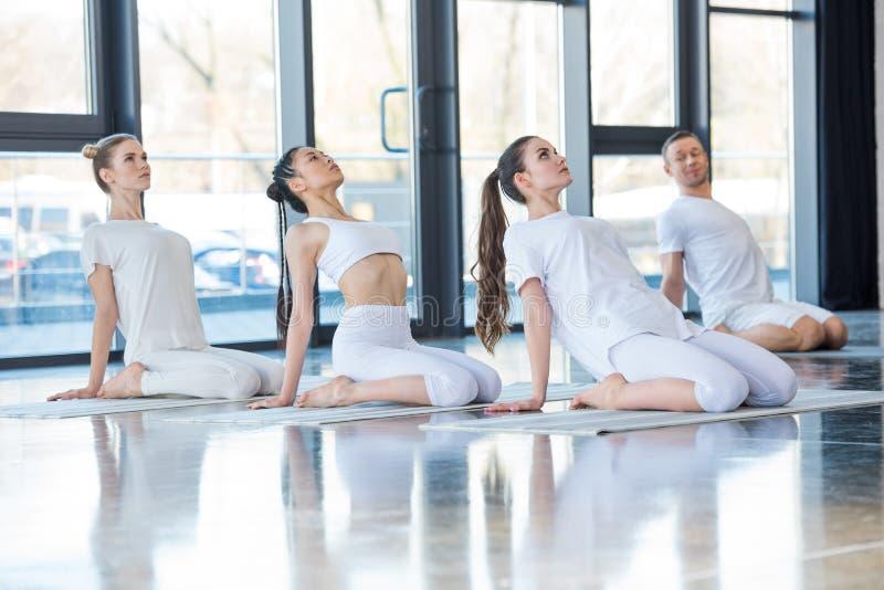 Vrouwen die yoga op matten samen met trainer uitoefenen stock foto