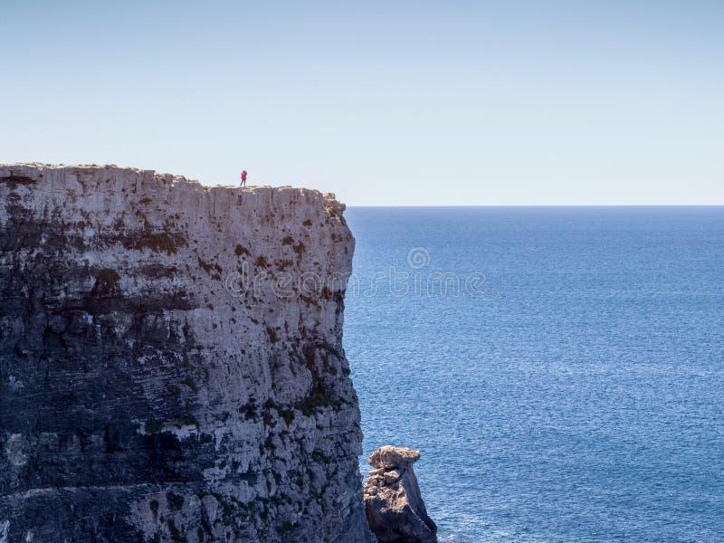 Vrouwen die zich hoogste van de hoge rots over het overzees bevinden stock foto