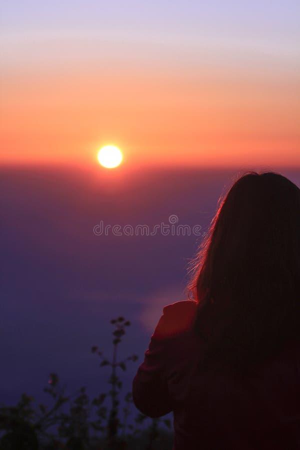 Vrouwen die zich op de berg bevinden die op de zonsopgang letten royalty-vrije stock foto