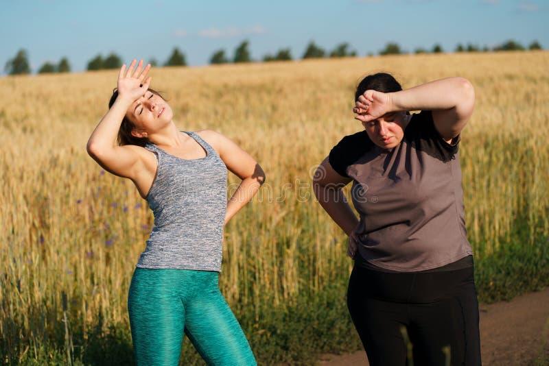 Vrouwen die zweet en rust na openluchtjogging afvegen stock afbeeldingen