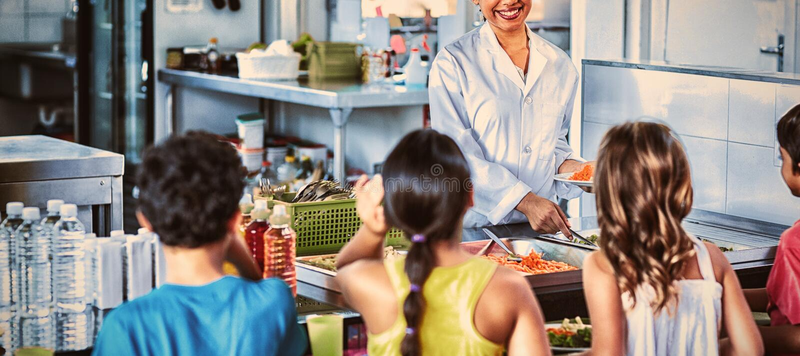 Vrouwen dienend voedsel aan schoolkinderen stock afbeelding