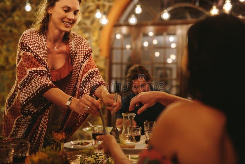Vrouwen dienend voedsel aan vrienden bij dinerpartij stock foto