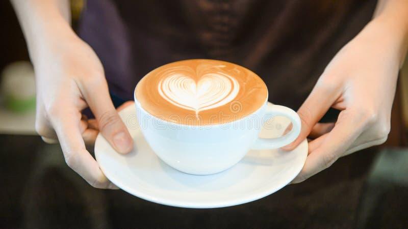 Vrouwen dienende koffie terwijl status in koffiewinkel Nadruk op Latte-de vormkop van de kunsthaard in vrouwelijke handen terwijl stock foto