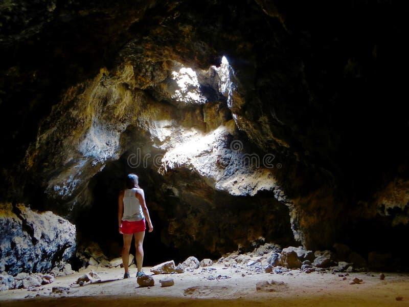 Vrouwen in donker hol van Lava Tubes stock afbeeldingen