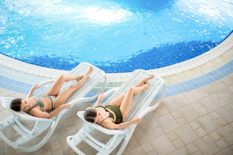 Vrouwen door zwembad stock foto's