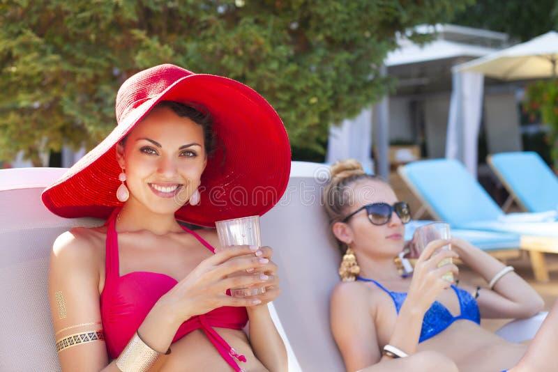 Vrouwen drinken cocktails terwijl het ontspannen door het zwembad royalty-vrije stock fotografie