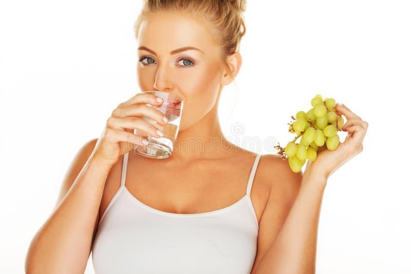 Vrouwen drinkwater en etend druiven stock foto