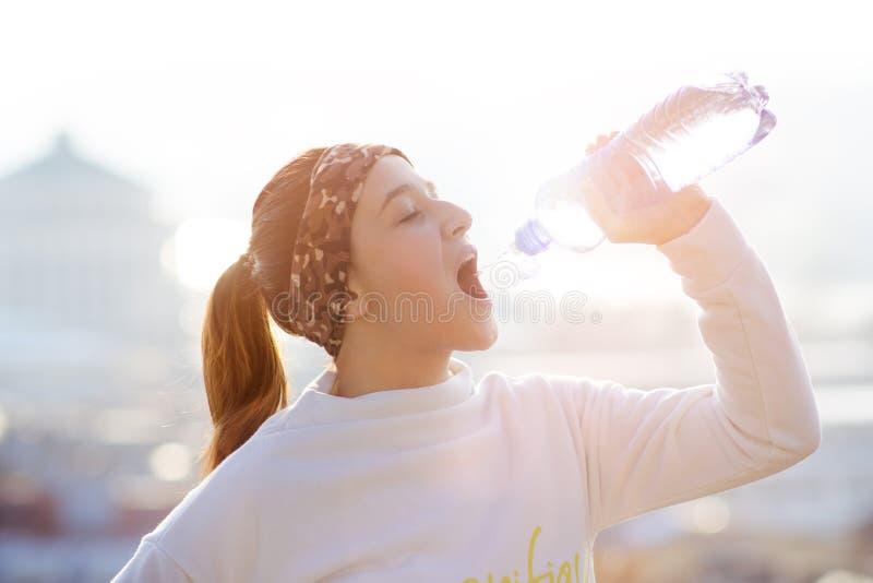 Vrouwen drinkwater tijdens het lopen De herfst Koud weer Joggingvrouw in een stad tijdens de winter Zonnige dag Het drinken wijze royalty-vrije stock afbeeldingen