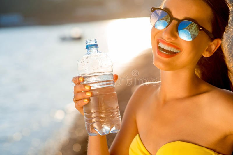 Vrouwen drinkwater van transparante fles  stock foto