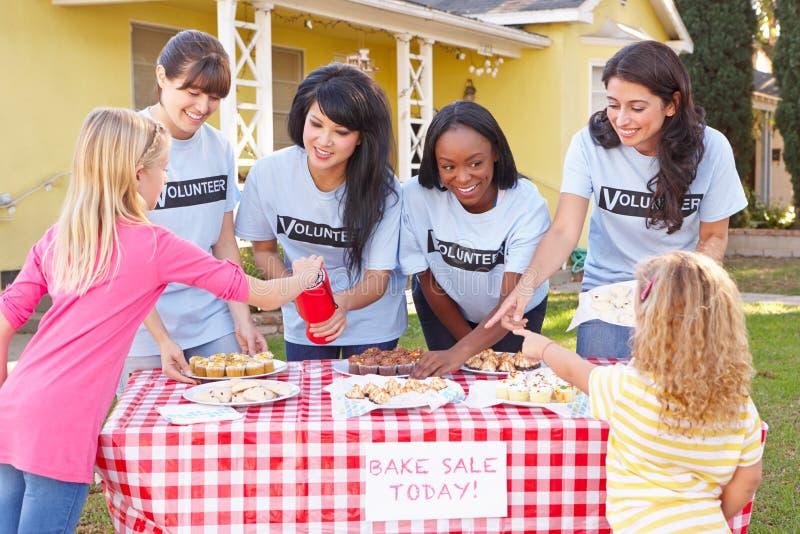 Vrouwen en de Kinderen die Liefdadigheid de in werking stellen bakken Verkoop royalty-vrije stock foto