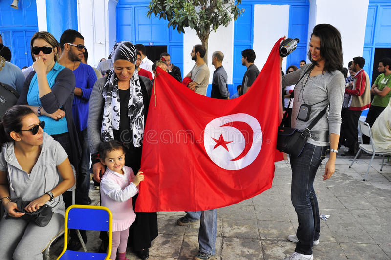Vrouwen en kind die rode vlag houden wachtend te stemmen royalty-vrije stock foto's