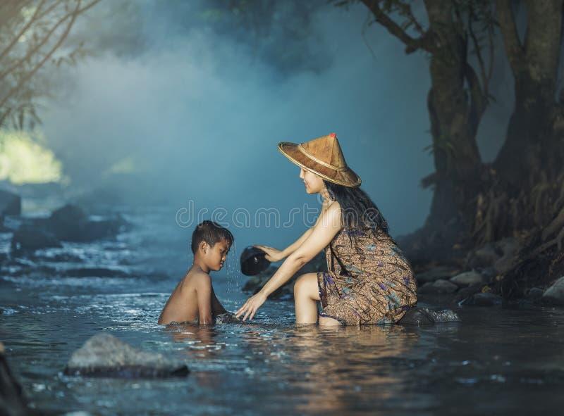 Vrouwen en kinderen die de stroom spelen stock afbeelding