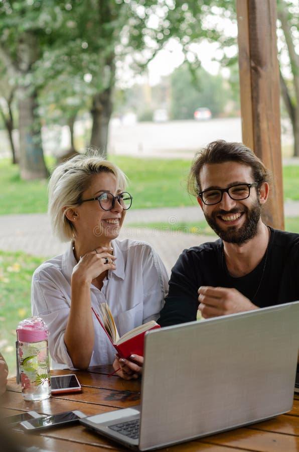 Vrouwen en mannen die in het park met tabletcomputer werken royalty-vrije stock foto