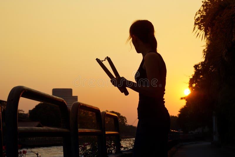 Vrouwen en nunchaku in handensilhouet in zonsondergang, vechtsporten stock foto
