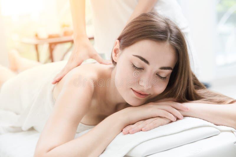 Vrouwen gelukkig om de massage van de rugpijnhulp in kuuroord te ontspannen royalty-vrije stock foto