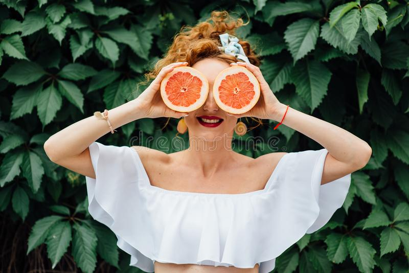 Vrouwen geschikt meisje die twee halfs van grapefruit houden royalty-vrije stock foto
