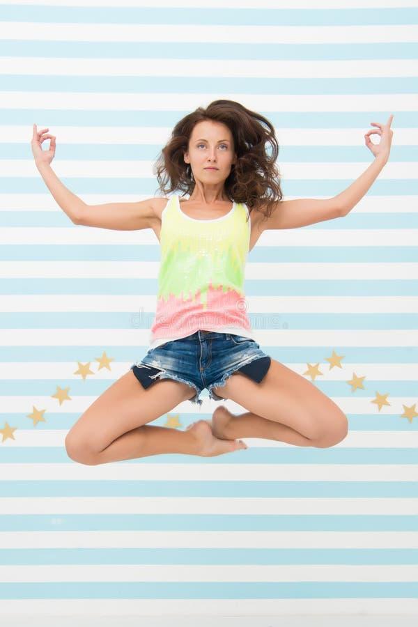 Vrouwen geschikte slanke dame die zoals mediterend terwijl sprong medio lucht stellen De gezonde levensstijl houdt u in goede ste stock fotografie