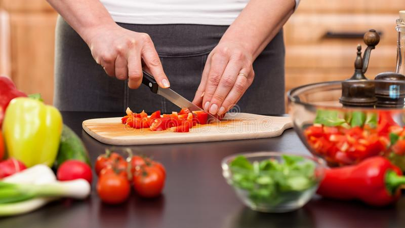 Vrouwen hakkende groenten voor een salade - close-up op handen royalty-vrije stock afbeeldingen