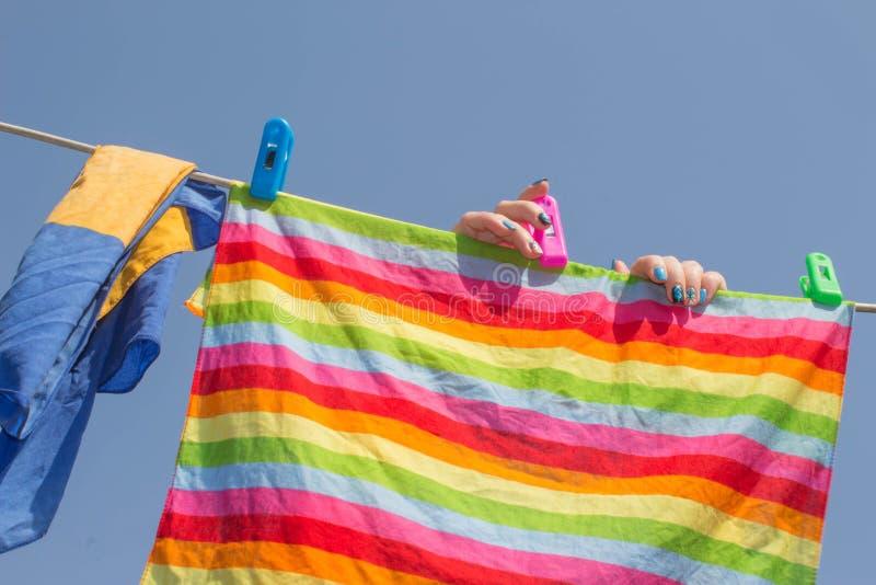 Vrouwen hangende handdoek op drooglijn na wasserij in de zon op de achtergrond van de onduidelijk beeldaard, goed weer bij de zom stock afbeeldingen