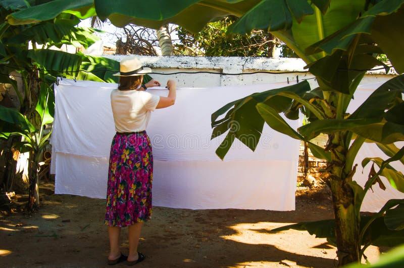 Vrouwen hangende wasserij op een waslijn stock fotografie